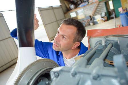 a mechanic inspecting aircraft propellor Stock Photo