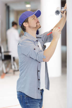contractor installing a camera in a clinic