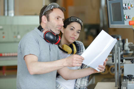 man and woman reading paperwork before using machine