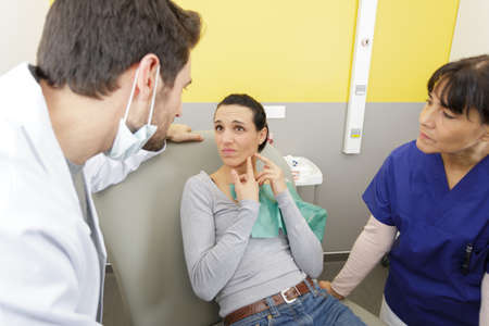 female patient showing source of pain to dentist