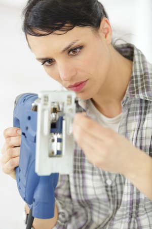 serious middle-aged professional female carpentry fixing an electric drill Stockfoto
