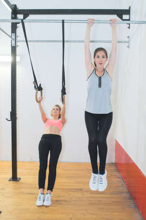 two women in sportswear training indoors at sports hall