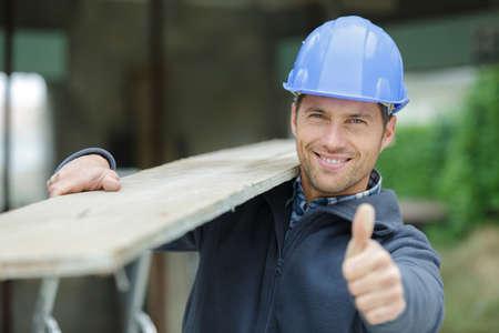furniture maker carrying wood planks on his shoulder