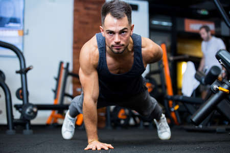 portrait of a concentrated young sportsman doing plank exercise