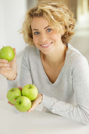 an attractive woman holding apples