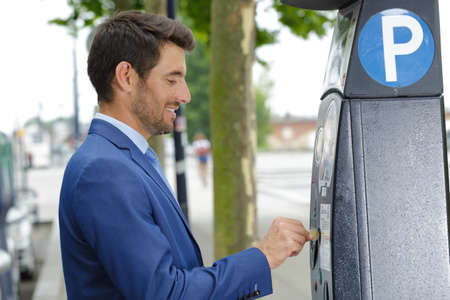 businessman putting coins in a parking meter Stock Photo