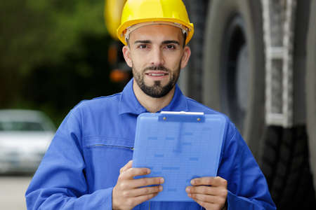 portrait of young mechanic wearing hardhat with clipboard