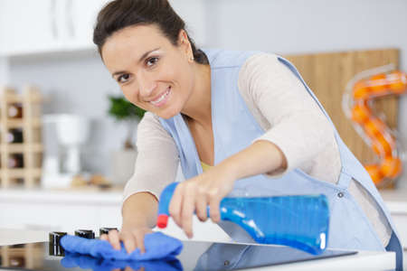 beautiful housekeeper cleaning the kitchen Imagens