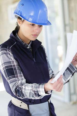 female builder on site looking at paperwork