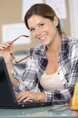 portrait of happy female computer technician using laptop Archivio Fotografico