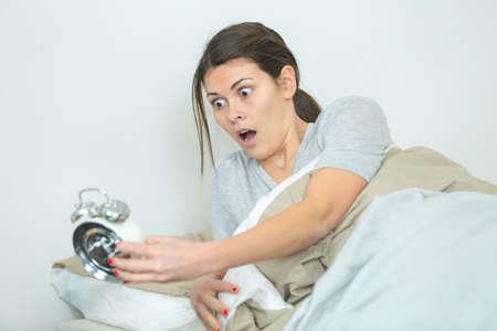 woman oversleeping and realising time on alarmclock