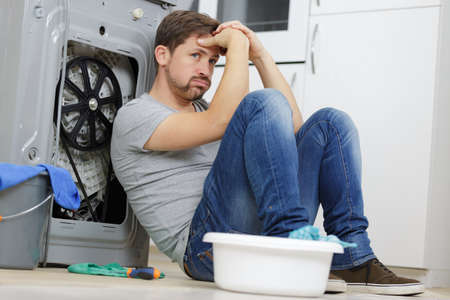 upset man sitting next to dishwasher Reklamní fotografie