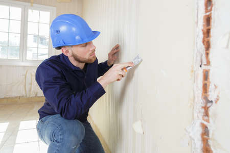 young builder removing wall paper Banque d'images - 140990833