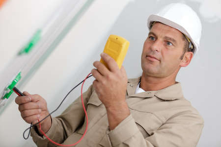 mature male electrician using a multimeter Banque d'images