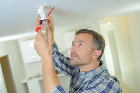 mature handyman changing bulb at clients home Foto de archivo