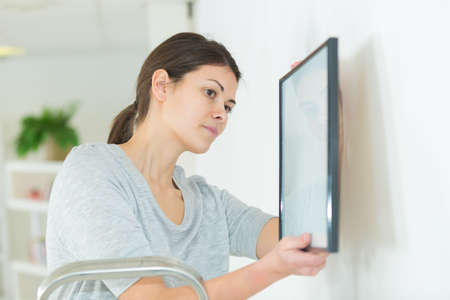 young woman putting frame on white wall at home Stock Photo