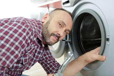 portrait of mature serviceman by washing machine