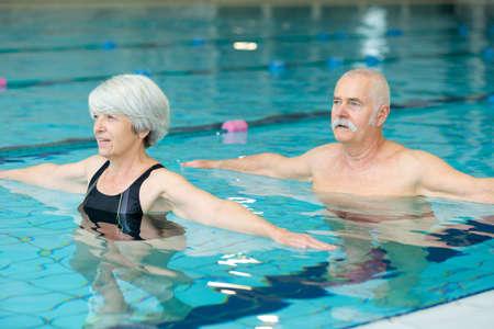 male and female elders doing aqua exercises