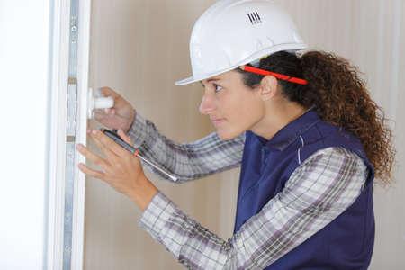 female builder on door knob installation