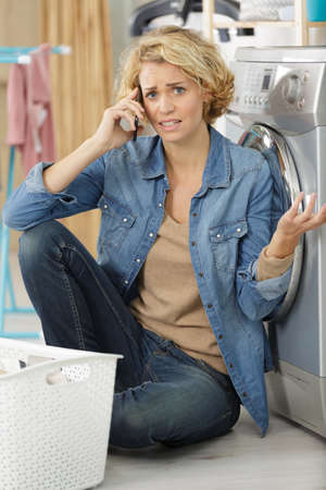 distressed woman by washing machine making call on smartphone Reklamní fotografie