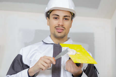 young plasterer concrete worker at wall