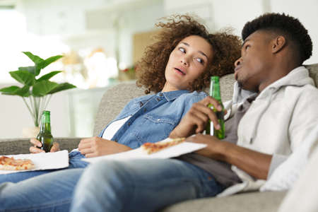 couple leaning back on the sofa holding beers and pizza