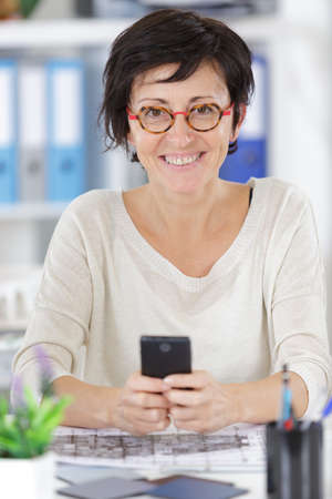 woman holding her phone phone in modern office