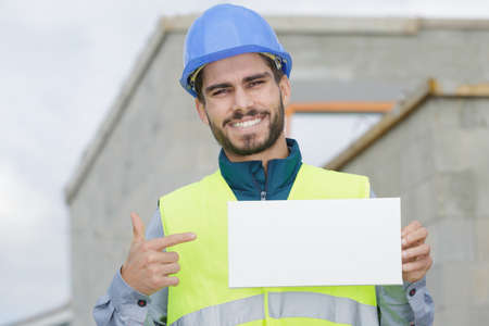 smiling young worker holding a white placard
