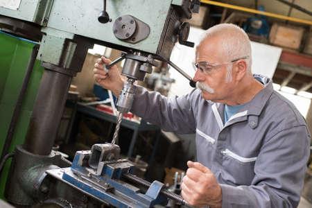 senior worker using bench drill