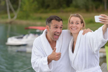 couple in bathrobes taking selfie photograph