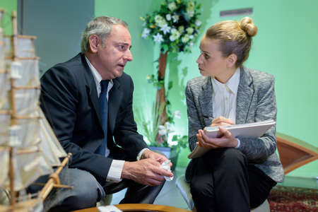 female funeral director talking to mature man