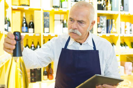 senior shop assistant in wine department holding digital computer