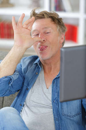 man thumbing his nose during video chat on tablet