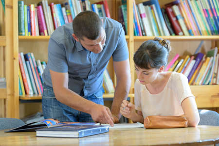 male teacher working with college student in library