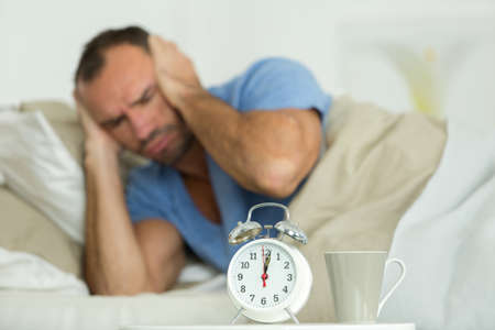 man in bed covering ears from noisy alarm clock Stock Photo