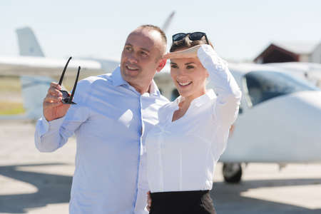 portrait of two business people standing by plane