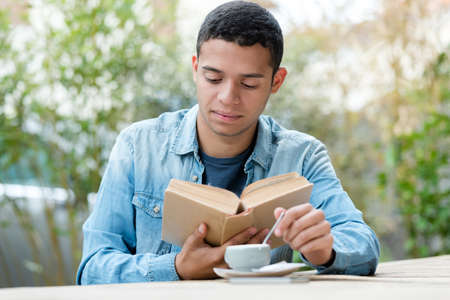 handsome young man drinking coffee while reading book 版權商用圖片