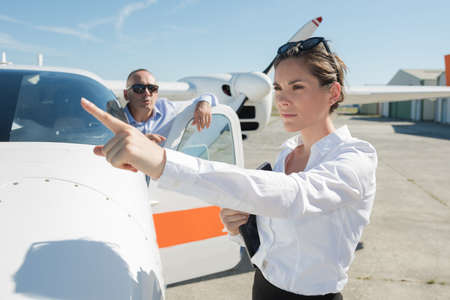 woman pointing at distance beside private aircraft