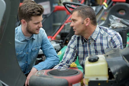 men checking lawn mower Stock Photo