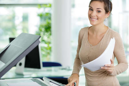 happy woman photocopying in her office