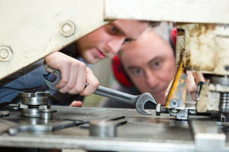 apprentice tightening bolt on machinery with spanner