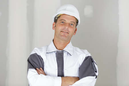 happy smiling worker in uniform with crossed arms