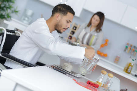 man on the wheelchair serving himself with water