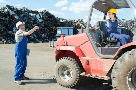 woman driving dumper truck in scrap yard