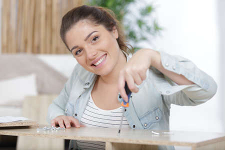 a happy woman building furniture