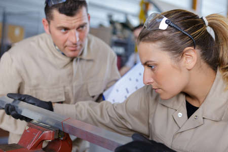 female worker clamps metal in a vice
