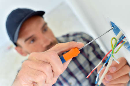 Electrician wiring a new build Stock Photo