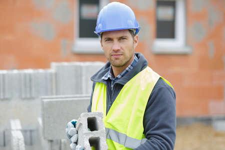 male builder installing concrete blocks Stockfoto
