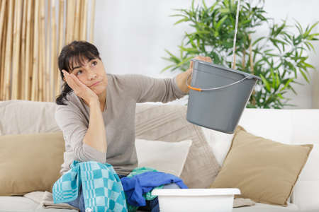 frustated woman having water leaks sitting on a couch