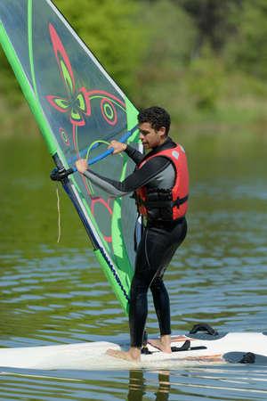 a nice sportman is doing windsurf